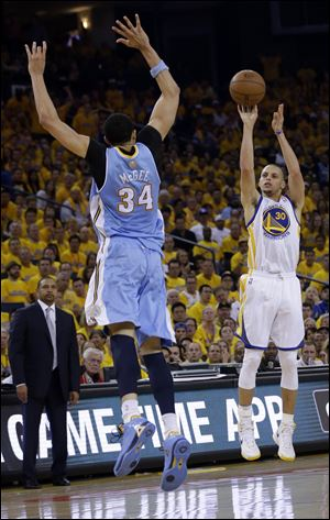 Golden State Warriors' Stephen Curry (30) shoots over Denver Nuggets' JaVale McGee (34) during the first half of Game 6.