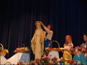 Brittanie Kuhr crowns a statue of Mary in 2009.