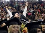 Eric Bernardo of Springfield, Ohio, celebrates graduation during commencement ceremonies at the BGSU Stroh Center Saturday.