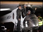 Solar Impulse co-founder, pilot and CEO Andre Borschberg, left, greets pilot Bertrand Piccard at Sky Harbor International Airport in Phoenix after completing the first leg of its coast-to-coast flights across the United States.