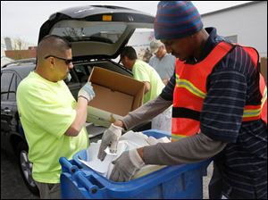 AccuShred employees Juan Bahena, left, and Melvin Harris Jr., right, dump documents into a bin before shredding them for a local resident.