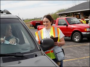 Wood County Solid Waste District environmental educator Amanda Gamby, right, talks with a local resident while writing her a receipt during the recycling drop off day.