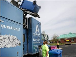 AccuShred employee Juan Bahena watches as a bin of documents is loaded into the company's mobil shredder.