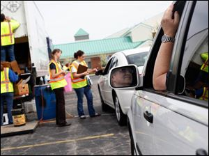 Barry Deutsch, of Perrysburg, right, waits in his car for his turn to deposit his recycling.