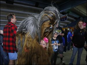 Abby Kurdziel, 4, gets a hug from Chewbacca on the concourse before the game. The Holland girl was with her family for Saturday night's theme game which was May the Fourth Be With You.