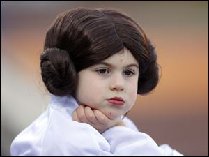 Copelin Martinovich, 4, is dressed as Princess Leia while she watches the game with her family from Battle Creek, Mich. Saturday night's Star Wars theme - May the Fourth Be With You.