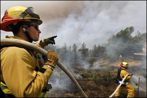 Firefighters from Riverside, Calif. work to extinguish a brush fire at Point Mugu, Calif.