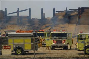 Fire trucks keep an eye on a burned structure at the Naval Base Ventura County at Point Mugu, Calif.
