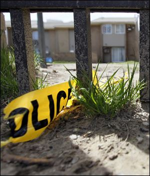 A piece of yellow police tape is caught on the gate surrounding the Greenbelt Place apartments last week.
