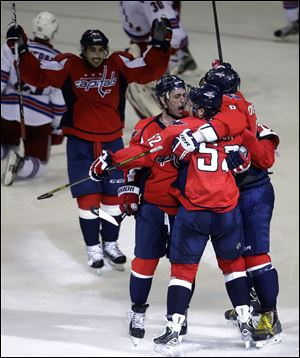 Washington Capitals defenseman Mike Green, second from right, is congratulated by teammates after he scored the game-winning goal in overtime.