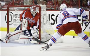 Washington Capitals goalie Braden Holtby makes a save against New York Rangers right wing Darroll Powe during the second period.