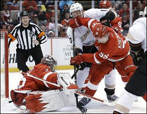 Wings defenseman Niklas Kronwall clears the puck from Anaheim's Corey Perry in front of Red Wings goalie Jimmy Howard during the first period.