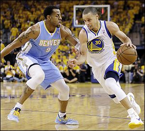 Golden State's Stephen Curry drives the ball against Denver's  Andre Iguodala.