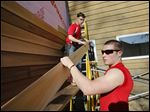Jonathan Wiemer, 17, of Ottawa Hills, left, and Corey Donnelly, 17, of Northview install siding on the Olander Park administration building in Sylvania on Wednesday.