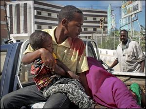 A Somali man carries a wounded child in the back of a pickup truck to a hospital, following a suicide car bomb blast in the capital Mogadishu, Somalia today.