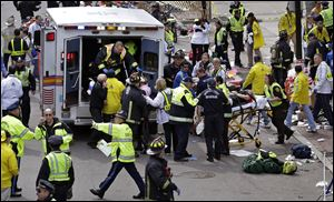 Medical workers aid injured people after two bombs exploded near the finish line of the Boston Marathon in Boston, April 15.