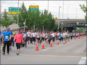 Thousands run and walk in a 5K on Saturday in front of the Cincinnati Bengals stadium as part of weekend-long events of the Flying Pig Marathon, now in its 15th year. A 5K and 10K on Saturday were sold-out, as were a half and full marathon set for today, with more than 33,000 participants