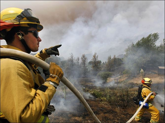 California Wildfire Firefighters from Riverside, Calif. work to extinguish a brush fire at Point Mugu, Calif.,  Friday.