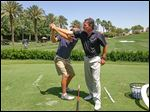 Mike Mitchell helps a golfer at a club in California where he is the course pro. A former Maumee resident, he has qualified for the Senior PGA Championship.