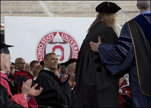 President Obama looks to famed photographer Annie Leibovitz, second from right, as she steps forward to receive an honorary doctorate during Ohio State University's spring commencement in the Ohio Stadium.