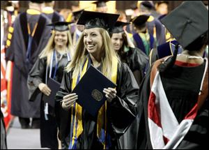 Sarah Hess, center, celebrates receiving her diploma during Sunday's commencement ceremony at the University of Toledo. With the end of the academic year, 3,041 students were eligible for degrees.