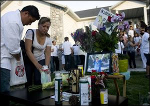 Alex Flores, left, and Silvia Castro place candles at a vigil for Ricardo Portillo, who passed away after injuries he sustained after an assault by a soccer player at a game he was refereeing on April 27.