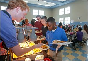 Ryan McIntosh serves chicken nuggets to Ka'ron Turner, right, Logan Jeziorowski, behind Ka'ron, and Charlette Hornyak, all seventh graders at Larchmont Elementary School. The school is testing six menu items to see if they make the grade at the school. Nine other schools are helping evaluate meals.