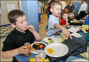 Patrick Ford eats a chicken nugget while Alejandro Lucio points to an item he liked on another first grader's plate.