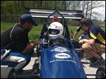 From the University of Toledo engineering team, A.J. Lesiecki talks strategy with driver Will Benson as part of a Formula race car event at Owens Community College.