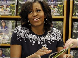 "First lady Michelle Obama signs copies of her book ""American Grown: The Story of the White House Kitchen Garden and Garden Across America"" at the Politics & Prose bookstore in Washington."
