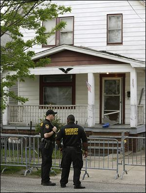 Sheriff deputies stand outside a house in Cleveland where Amanda Berry, Gina DeJesus, and Michelle Knight were found more than 10 years after they vanished.
