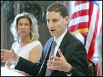 Ohio Treasurer Josh Mandel speaks to area business leaders, including Laura Glover of the Sylvania Area Chamber of Commerce, left, at the Wingate by Wyndham hotel in Sylvania.