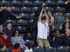 Fans reach for a foul ball that was thrown to them by a Mud Hens player in the dugout.