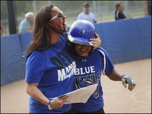 Springfield's assistant coach Krista Haley embraces Jacey Gray after scoring in the bottom of the second inning.