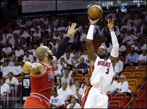 Miami Heat guard Dwyane Wade shoots against Chicago Bulls forward Carlos Boozer.