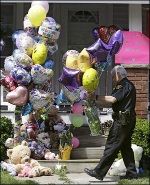 A Cleveland policeman carries balloons and flowers to the front porch of a home awaiting the arrival of Amanda Berry on Wednesday.