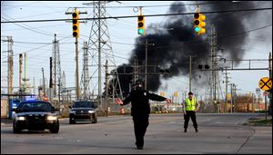 A  Melvindale police officer in a haz-mat mask directs traffic as a fire burns at the Marathon refinery in Detroit after an explosion April 27.