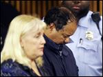 Ariel Castro and public defender Kathleen DeMetz, left, wait for his arraignment at Cleveland Municipal Court. Castro was charged with four counts of kidnapping and three counts of rape.  Ariel Castro was charged while his brothers, Pedro and Onil Castro, were held but faced no immediate charges.
