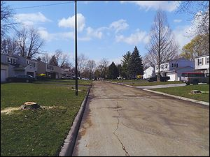 The top photo shows mature trees lining Cherrylawn Drive. The photo below that shows the same street minus the trees, which some Crossgates residents miss.