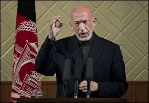 "Afghan President Hamid Karzai gestures during a ceremony at Kabul University in Kabul, Afghanistan, today. Karzai said he is ready to let the U.S. have nine bases in the country after the 2014 combat troop pullout, but wants Washington's ""security and economic guarantees"" first."