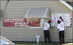 Guardian Angels hang a poster at the home of Gina DeJesus, one of three women freed on Monday.