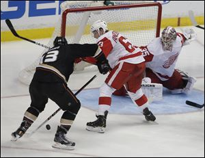 Anaheim Ducks center Nick Bonino, left, scores the winning goal past Detroit Red Wings' Joakim Andersson goalie Jimmy Howard and during overtime Wednesday in Anaheim, Calif.
