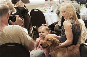 Mark Damschroder, left, snaps a photo of Maddie Conkey, 2, with her grandmother Lisa Damschroder and therapy dog Ginger, which they fostered.