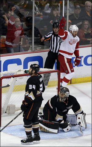 Detroit Red Wings left wing Johan Franzen, top, celebrates his goal past Anaheim Ducks goalie Jonas Hiller, bottom right, and Daniel Winnik.