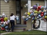 Culema Nevarez adds balloons to a growing tribute outside the home of Gina DeJesus in Cleveland.