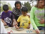 Amaan Omer, 10, works on crafting his own garden stone as his mother, Fareena Omer, center, helps his brother Ayman, 6, create another at Olander Park in Sylvania.
