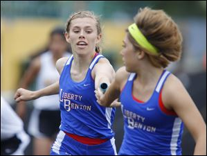 Liberty Benton runner Megan Peplinski, left, hands off to teammate Kara Shaffer during the 4x200 meter relay. The Eagles finished third in the race.
