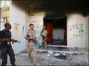 In September, Libyan military guards check one of the U.S. Consulate's burnt out buildings after the death of the American ambassador Chris Stevens and his colleagues in Benghazi.