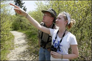 Autumn Rose McAllister, 14, of southern Ohio's Pike County points out a bird to her father, Martin McAllister, on a trail in Magee Marsh.
