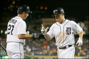The Tigers' Andy Dirks, right, celebrates with teammate Jhonny Peralta after hitting a solo home run during the seventh inning.
